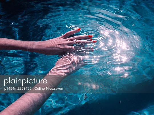 Woman hands in pool - p1484m2289438 by Céline Nieszawer