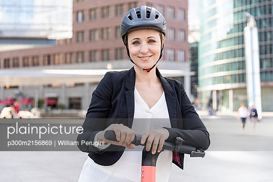 Portrait of smiling woman with e-scooter in the city, Berlin, Germany - p300m2156869 by William Perugini