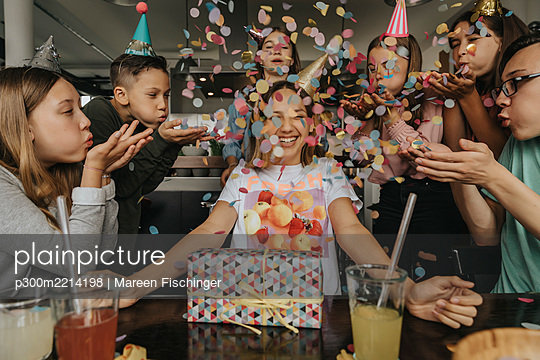 Happy friends throwing confetti on teenage girl sitting with birthday gift at dining table - p300m2214198 by Mareen Fischinger