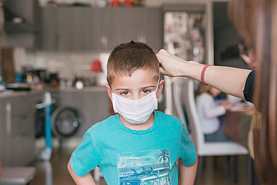 mother putting medical mask on her son to protect himself from the coronavirus - p1166m2182912 by Cavan Images