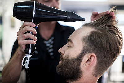 Barber blow-drying hair of a customer - p300m1166444 by zerocreatives
