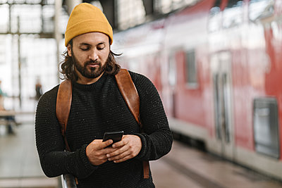 Young man using smartphone at the station platform, Berlin, Germany - p300m2155179 von Hernandez and Sorokina