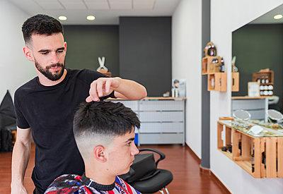 hairdresser combing a teenage boy, Matalascañas, Spain - p300m2275604 von Julio Rodriguez