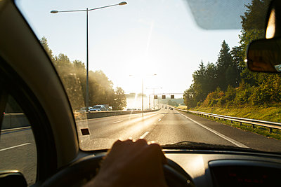 Sweden, Sodermanland, Man driving car on highway at sunset - p352m1126946f by Christian Ferm