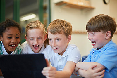 Schoolboys and girls laughing at digital tablet in classroom at primary school - p429m1547977 by Sydney Bourne