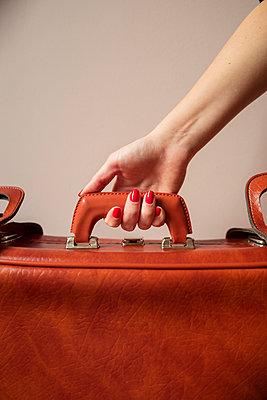 Frauenhand am Reisekoffer - p432m2157486 von mia takahara
