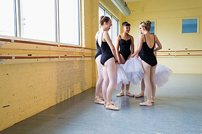 Girls standing and talking in ballet studio - p555m1491108 by Mark Edward Atkinson
