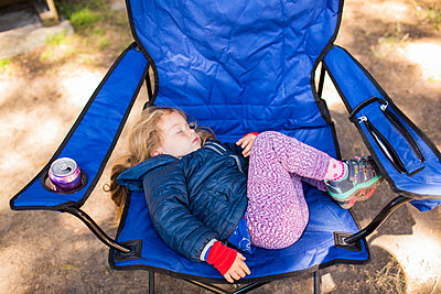 Caucasian girl sleeping on folding chair - p555m1521625 by Adam Hester