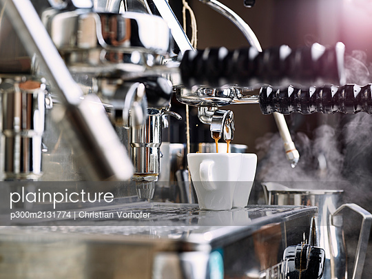 Two espresso cups getting filled in a portafilter machine - p300m2131774 by Christian Vorhofer