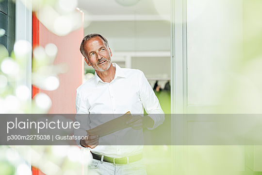 Thoughtful man with package looking away while standing at doorway - p300m2275038 by Gustafsson