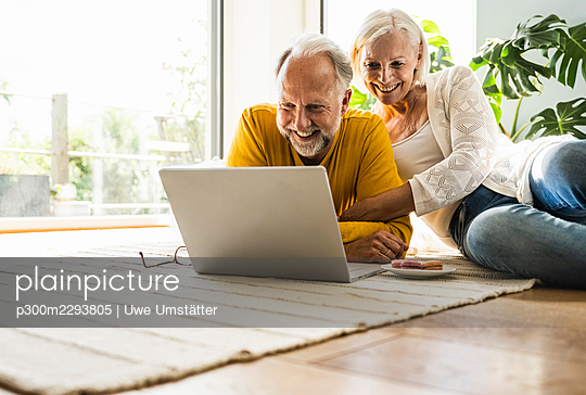 Smiling couple using laptop while relaxing on carpet at home - p300m2293805 by Uwe Umstätter
