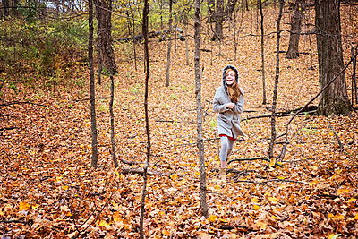 Young Red Hair Girl Playing Outside in Fall Leaves - p1166m2147047 by Cavan Images