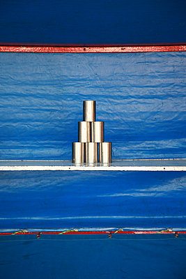 Stacked tin cans against blue background - p1685m2272473 by Joy Kröger
