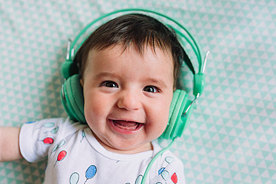 Portrait of laughing baby girl with headphones - p300m1459734 by Gemma Ferrando