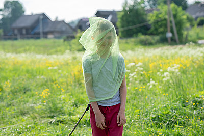 Playful boy wearing butterfly net while standing on grassy land - p300m2203163 by Vasily Pindyurin