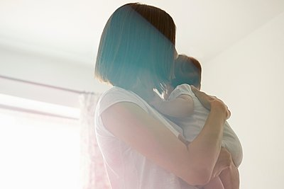 Mother carrying baby in bedroom - p429m1079990f by Emma Kim