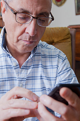 Hispanic man texting on cell phone - p555m1301697 by REB Images