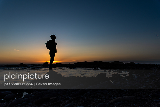 Silhouetted figure standing on rocky shore with sunset sky behind - p1166m2269384 by Cavan Images