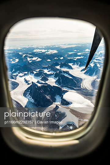 Aerial view of mountains and glaciers from plane window. - p1166m2292757 by Cavan Images