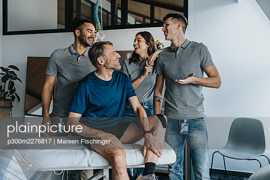Cheerful male physical therapists standing behind patient at massage table - p300m2276817 by Mareen Fischinger