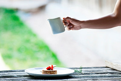 Cropped image of woman's hand holding jug over pancakes in plate - p1166m1144969 by Cavan Images