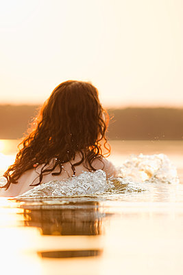 Woman bathing in lake at sunset - p1396m1589471 by Hartmann + Beese