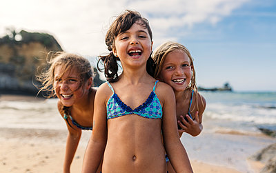 Spain, Colunga, three happy girls on the beach - p300m1188520 by Marco Govel
