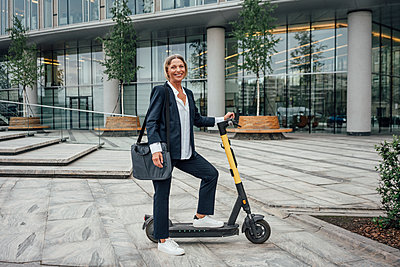 Female professional smiling while standing with electric push scooter at office park - p300m2294215 by Vasily Pindyurin