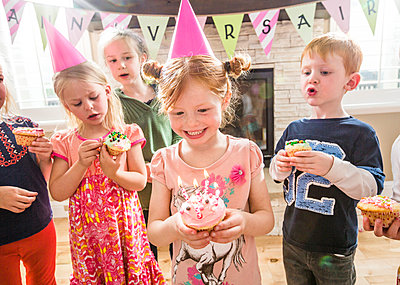 Caucasian girl wearing party hat holding cupcake with burning candles - p555m1304994 by Mike Kemp