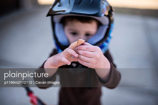 High angle view of boy wearing helmet showing bandage on wounded finger - p1166m2112112 by Cavan Images