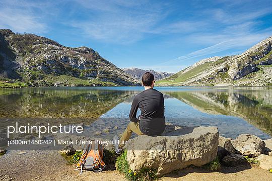 Spain, Asturias, Picos de Europa National Park, man sitting at Lakes of Covadonga - p300m1450242 by Maria Elena Pueyo Ruiz