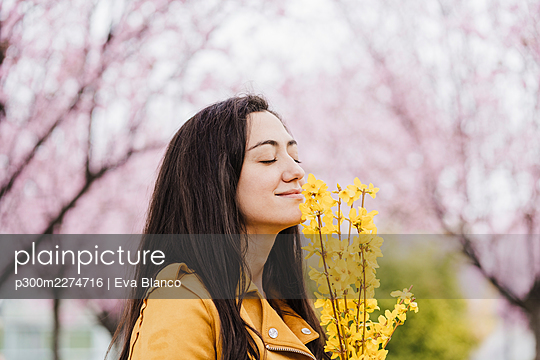 Smiling woman with eyes closed smelling fragrance of yellow flowers - p300m2274716 by Eva Blanco