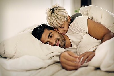 Portrait of smiling man lying with loving woman in bed at home - p1166m1096263f by Cavan Images