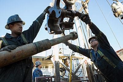 Male workers working drilling rig equipment gas plant - p1192m1128001f by Hero Images