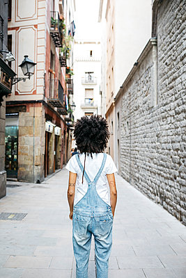 Spain, Barcelona, back view of woman with curly hair wearing dungarees - p300m2024090 von Josep Rovirosa