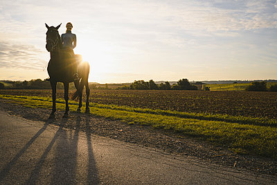 Woman on horse in the countryside at sunset - p300m2156347 by Joseffson