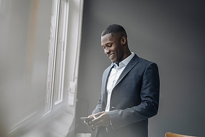 Smiling young businessman standing near window looking at cell phone - p300m2167317 von Kniel Synnatzschke