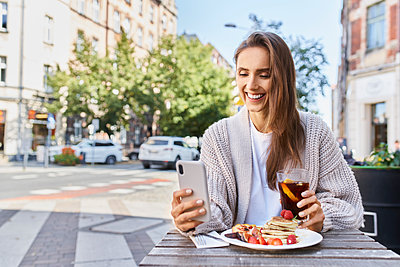 Smiling woman using mobile phone while having breakfast at sidewalk cafe - p300m2225082 by Bartek Szewczyk