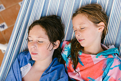 Brother and sister in bathrobe sleeping in hammock - p300m2281386 by Lightsy Studio