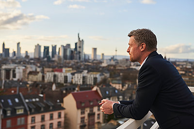 Thoughtful mature businessman standing at rooftop in city - p300m2281418 by Annika List