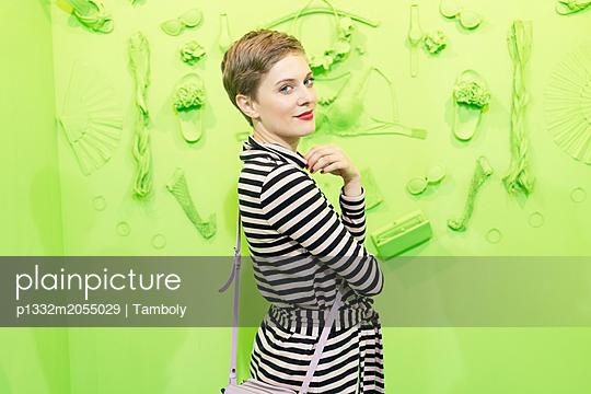 Blonde Frau vor einem grünen Hintergrund - p1332m2055029 von Tamboly