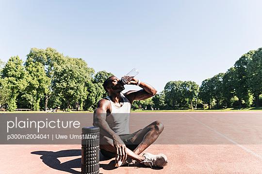Young athlete sitting on sports field, drinking water - p300m2004041 von Uwe Umstätter