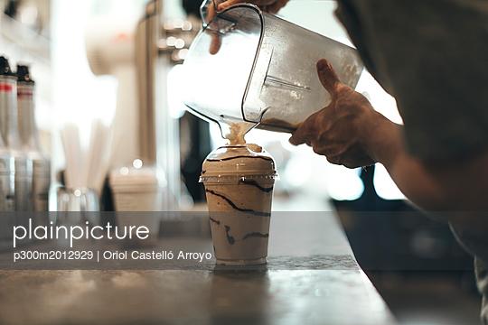 Man preparing coffee delicacy in a coffee bar - p300m2012929 von Oriol Castelló Arroyo