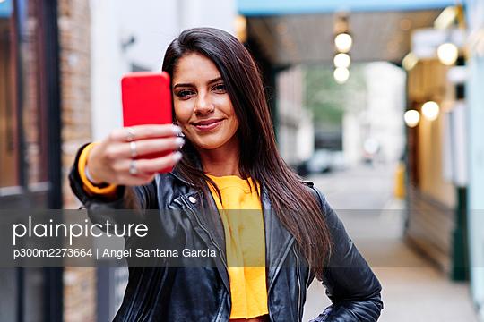 Smiling woman taking selfie through mobile phone in city - p300m2273664 by Angel Santana Garcia