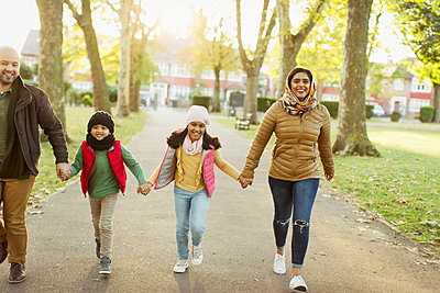 Happy Muslim family holding hands, walking in autumn park - p1023m2087930 by Robert Daly