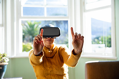 Mature woman alone at home in VR headset - p1315m2131240 by Wavebreak