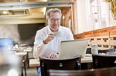 Portrait of confident mature businessman in cafe using laptop - p300m1417225 by Jo Kirchherr