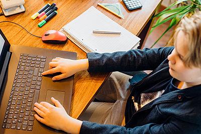 Boy sitting at desk using laptop - p300m2189425 by Jana Mänz