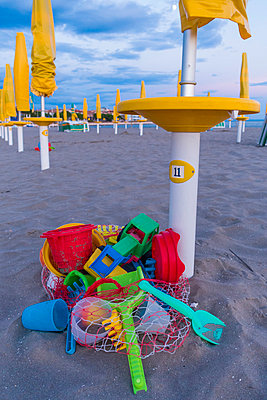 Italy, Friuli-Venezia Giulia, closed beach umbrellas and toys on the beach of Grado - p300m975444f by Karl Thomas