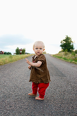 Baby girl standing on a rural road in Smaland, Sweden - p352m2039825 by Julia Sjöberg